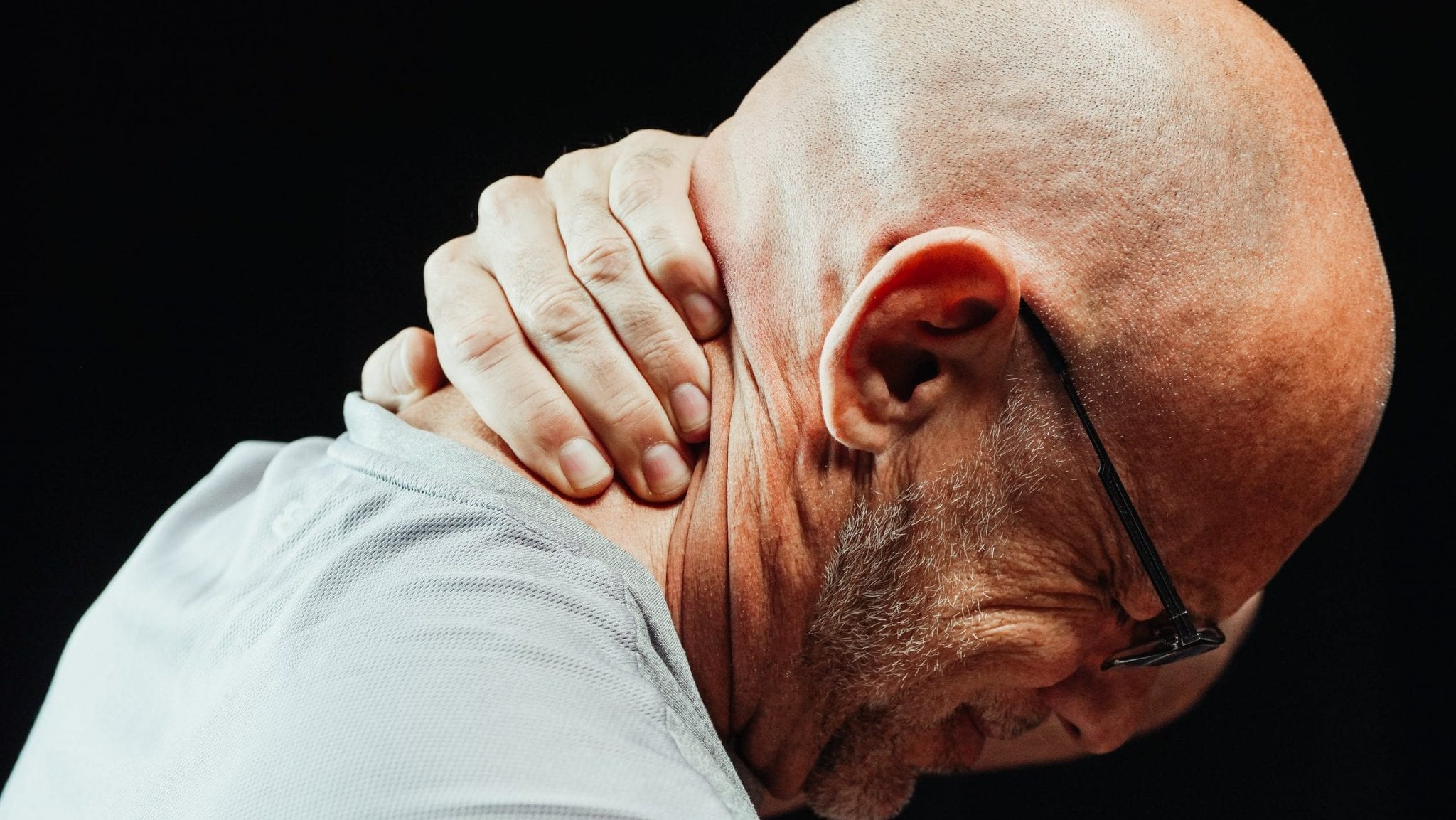 Man holding the back of his injured neck