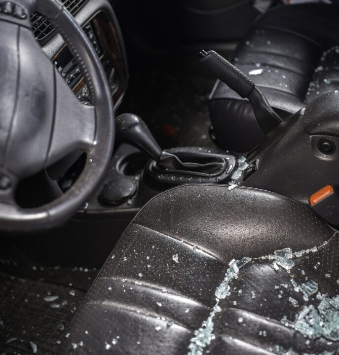 vandalized car with glass on driver seat