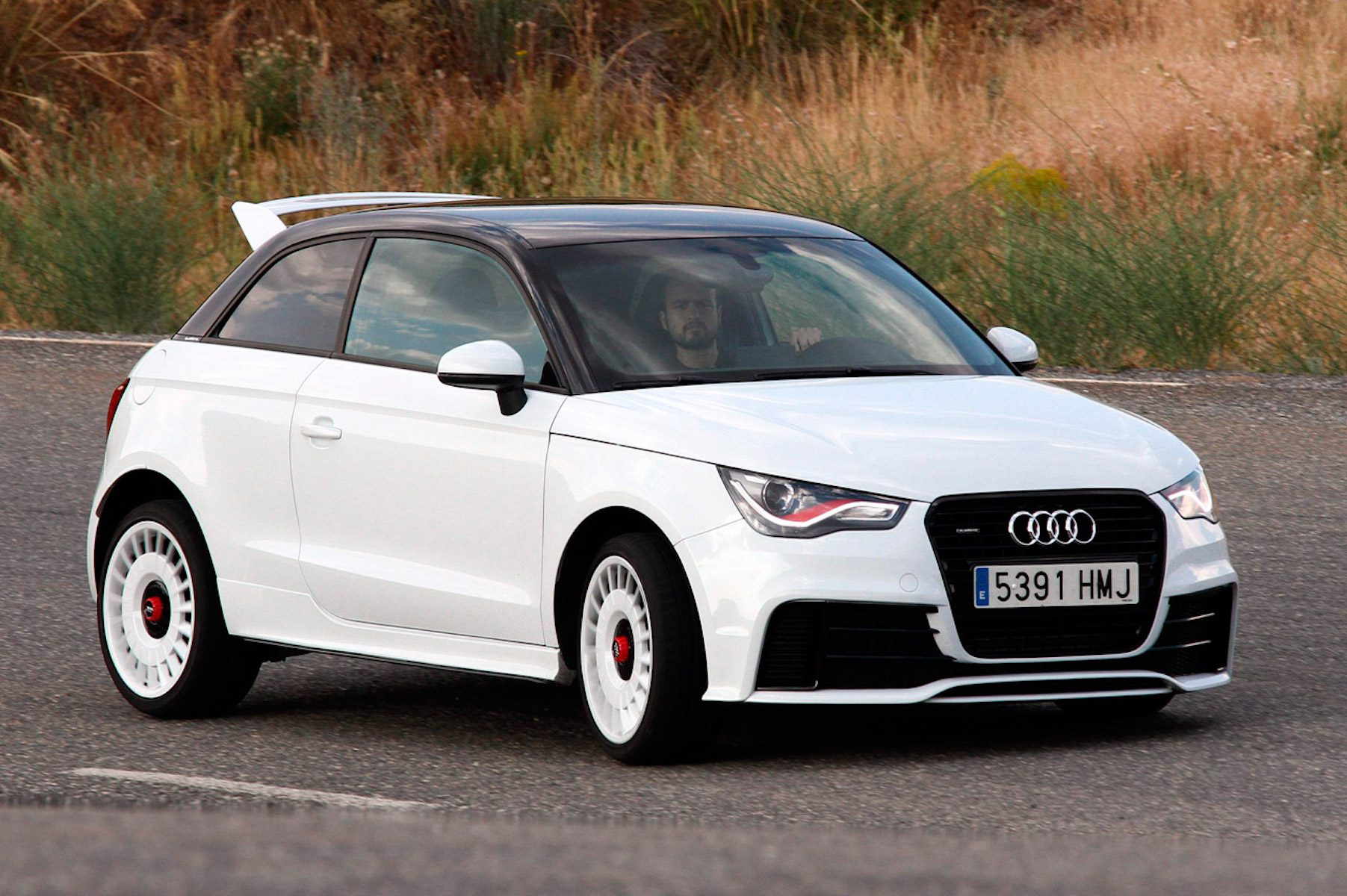 A side view of a driver enjoying his ride in the 2011 White Audi A1 Quattro Coupe