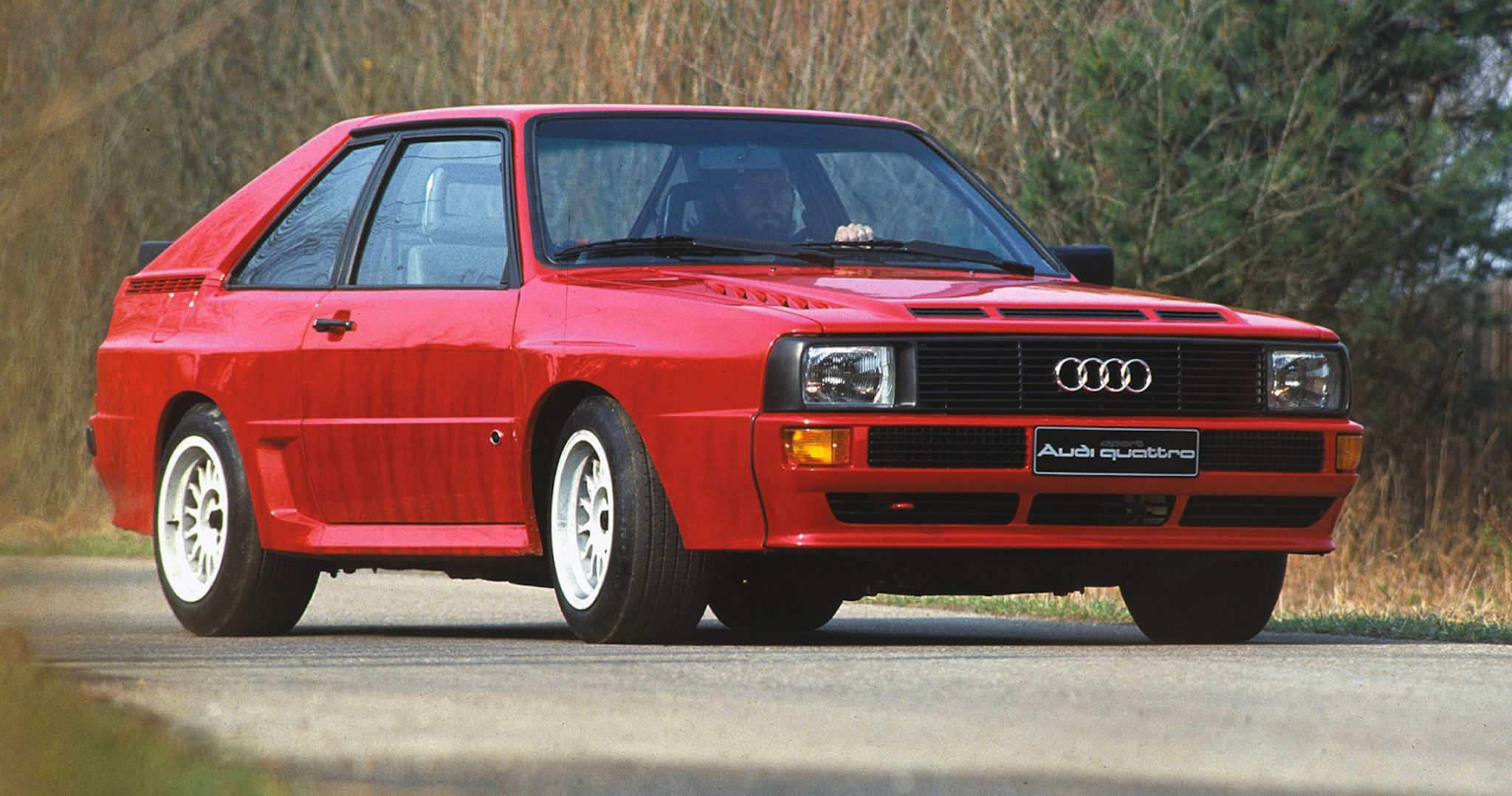 A side view of a red 1980 Audi Quattro Coupe on a road.