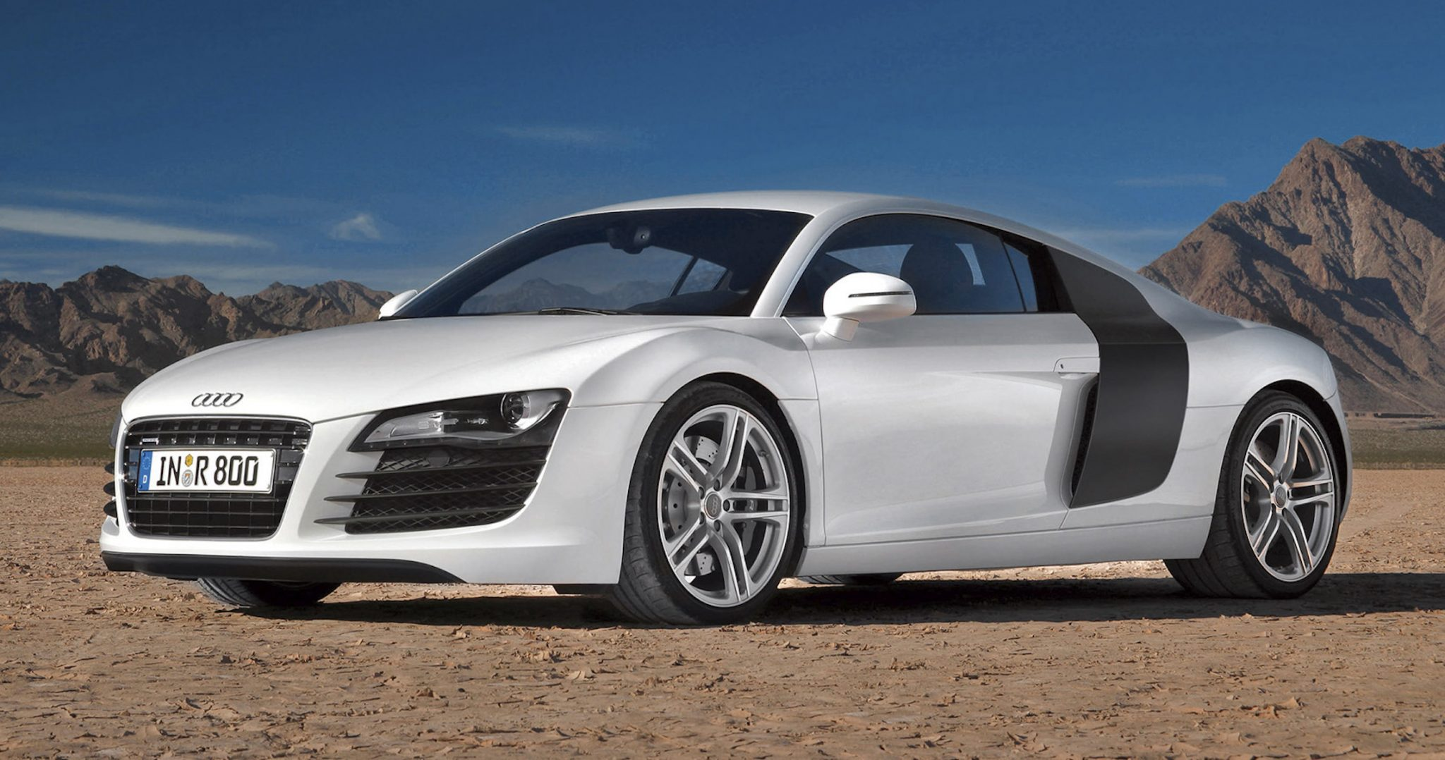A side view of a white First Gen Audi R8 in a desert