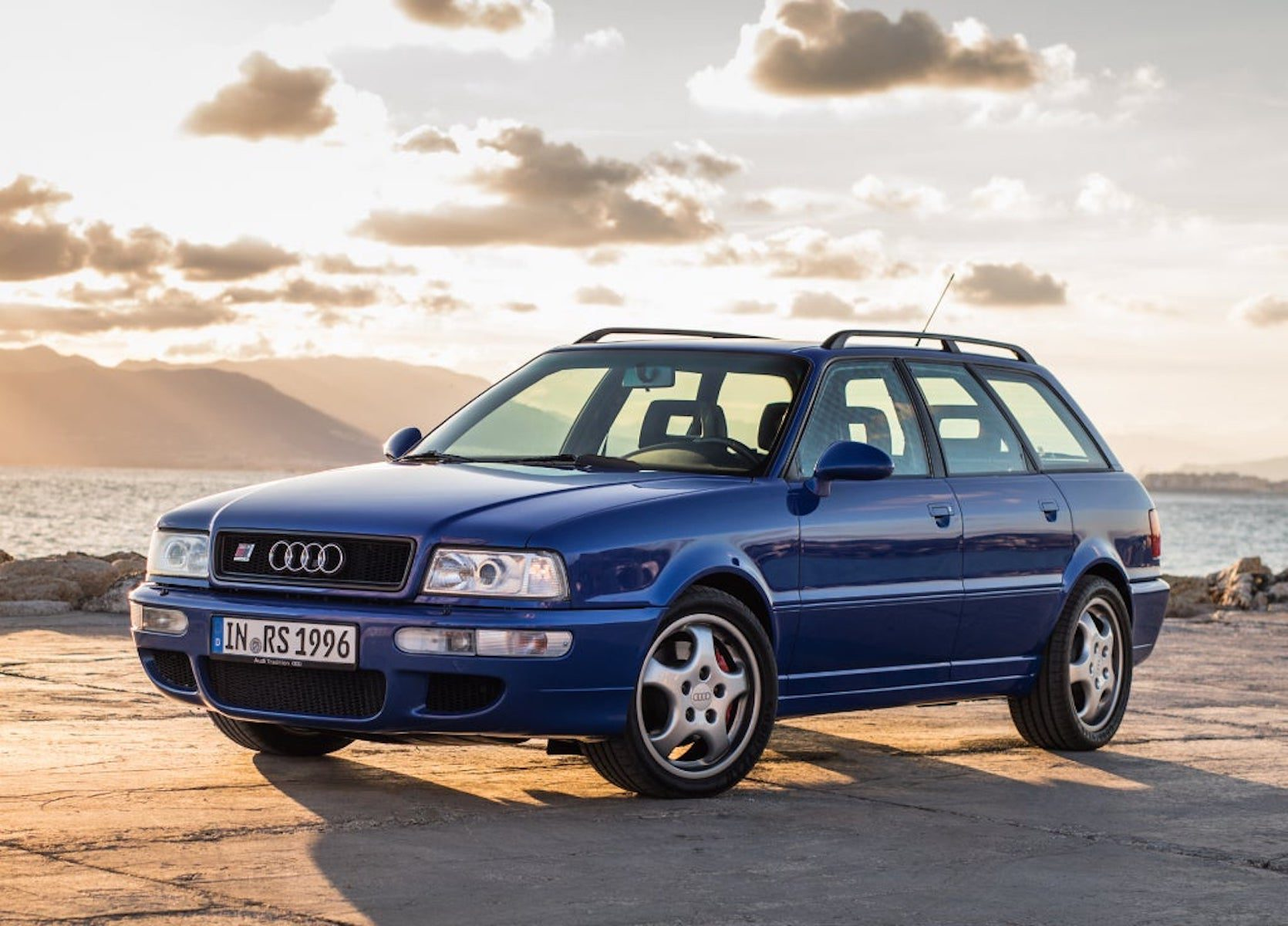 A side view of a blue 1994 Audi RS2 Avant Station Wagon in front of a lake