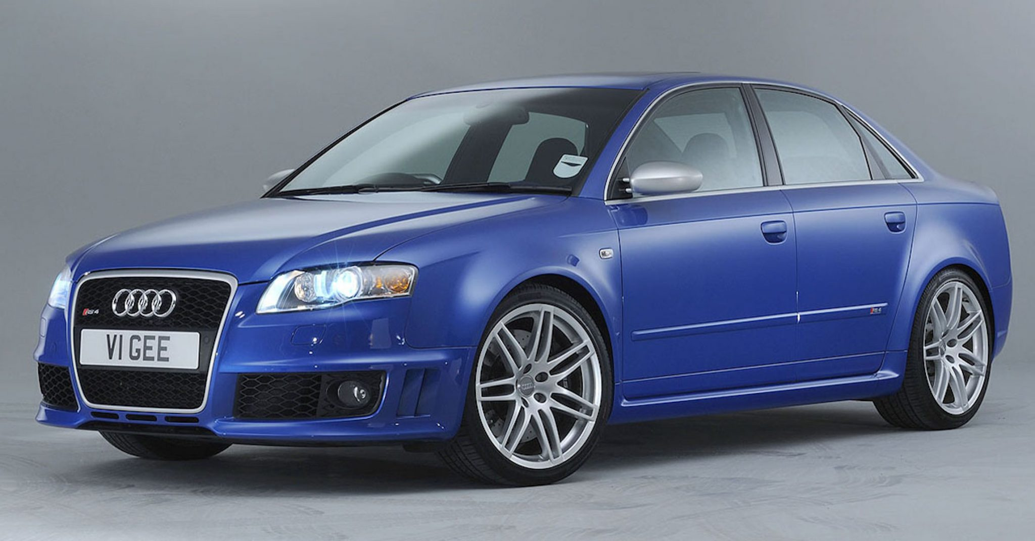 A side view of a blue 2006 Audi RS4 B7 Sedan in a photography studio