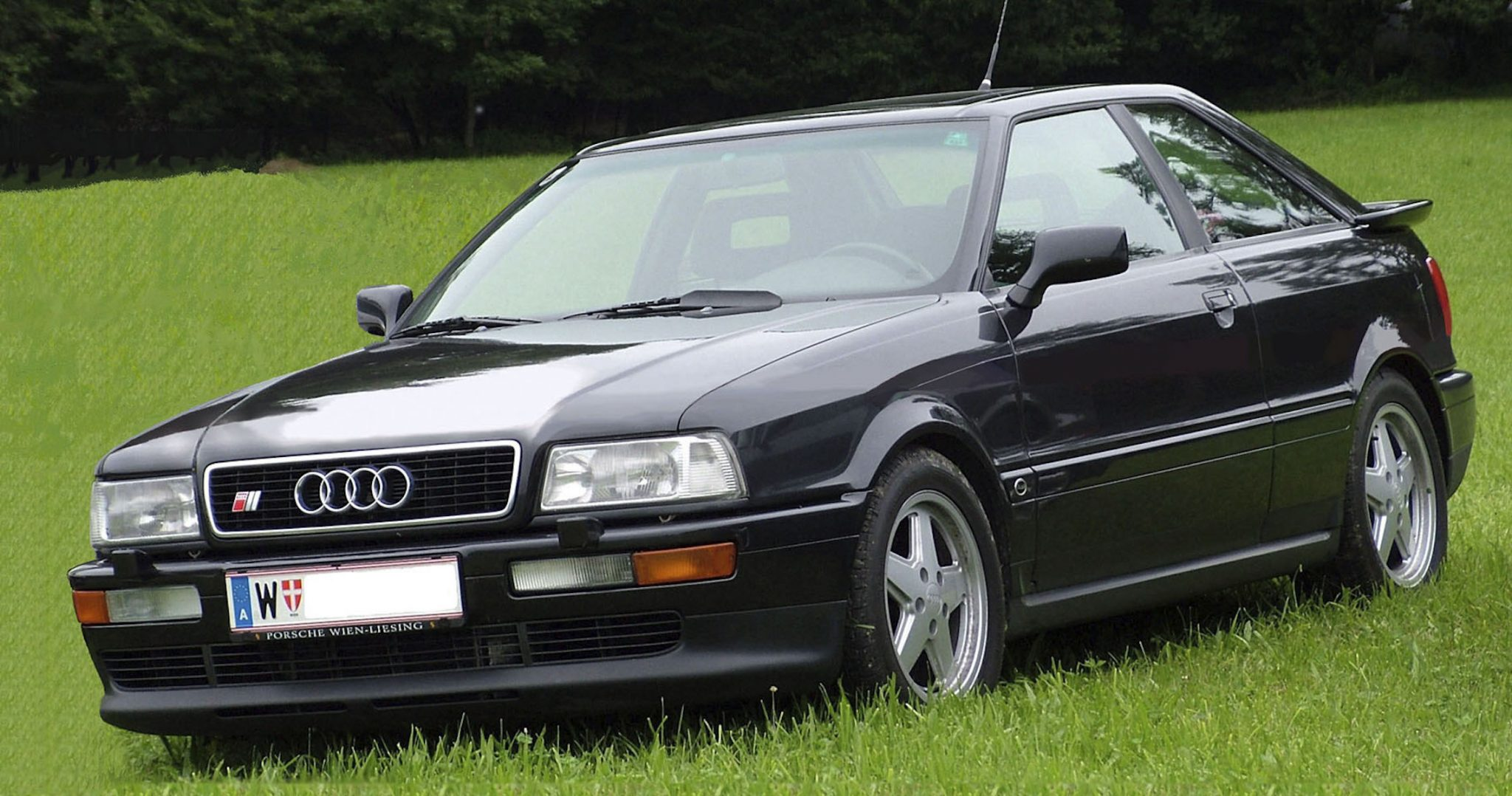 A side view of a black 1990 Audi S2 Coupe parked in the grass