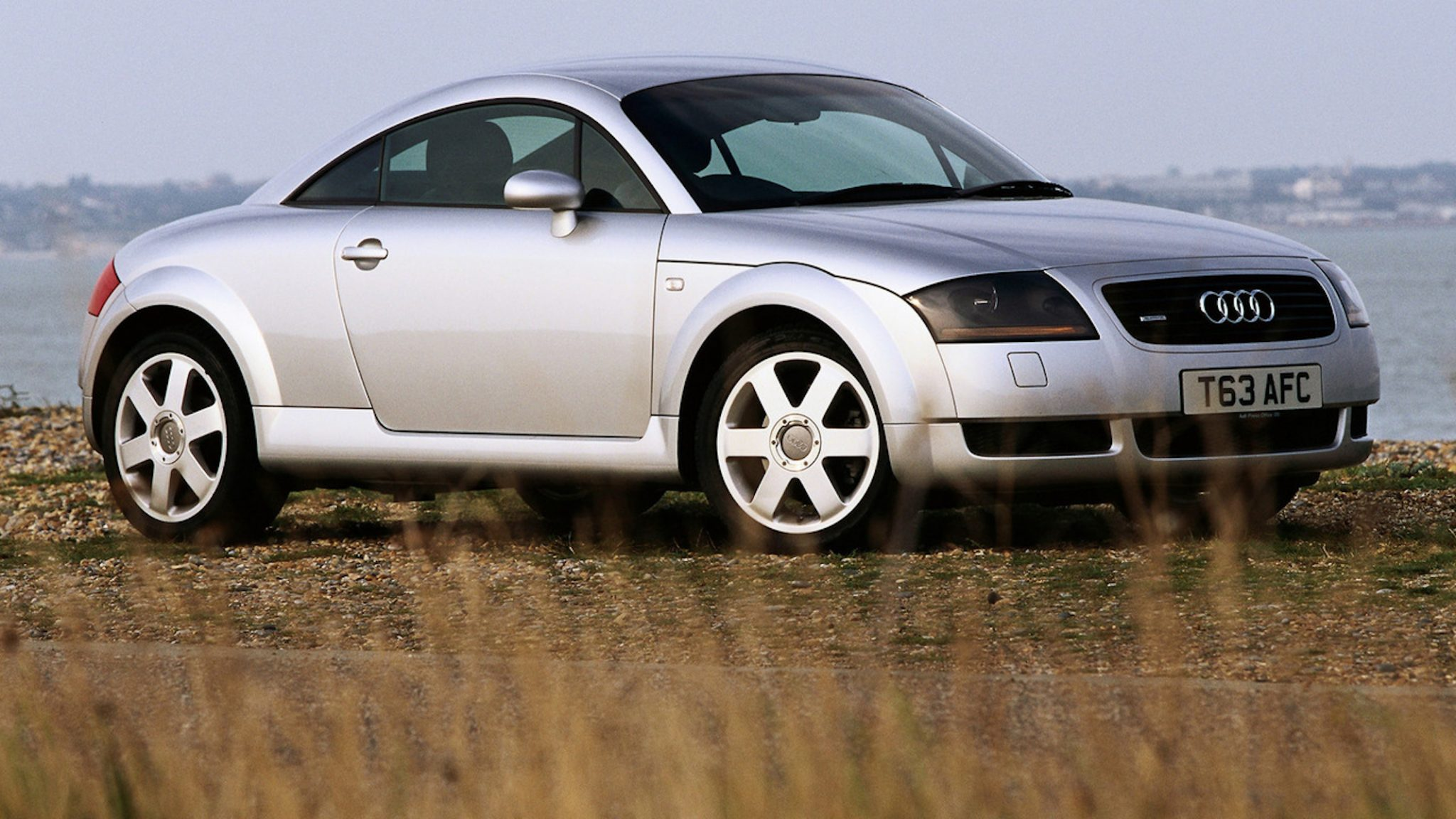 A side view of a silver First Gen Audi TT Coupe in front of a large body of water.