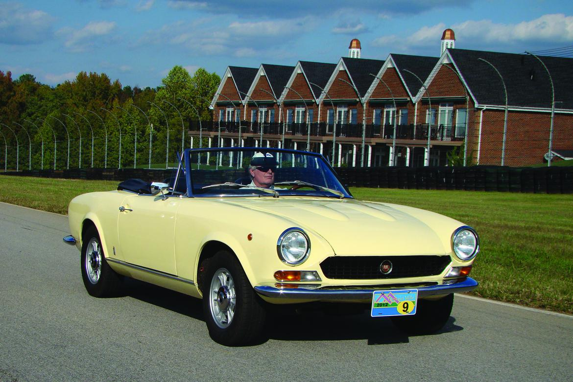 Pale yellow 1966 Fiat 124 Spider passing row of houses on rural road