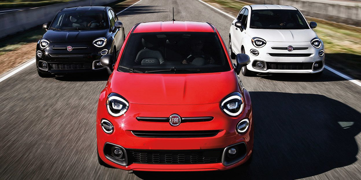 Three Fiat 500x Crossover cars in red and white and blue racing down road