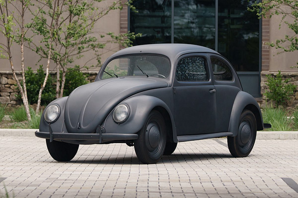 A side view of a 1943 matte black VW Beetle in a parking lot