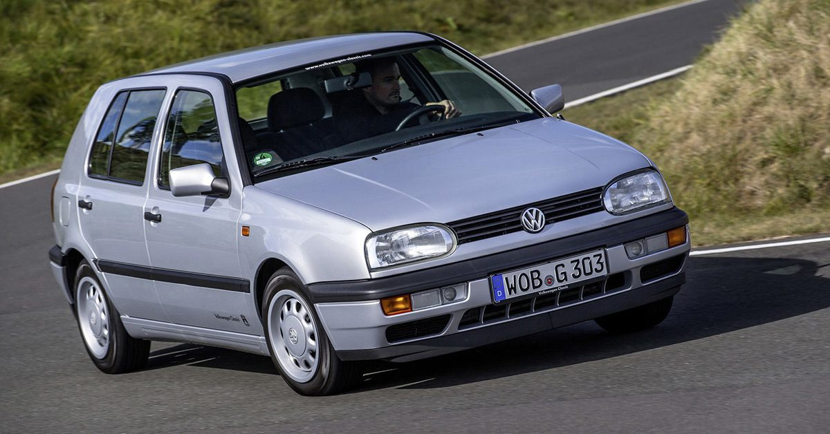 A side view of a rider enjoying a drive on a twisty road with his Silver four-door MK3 VW Golf
