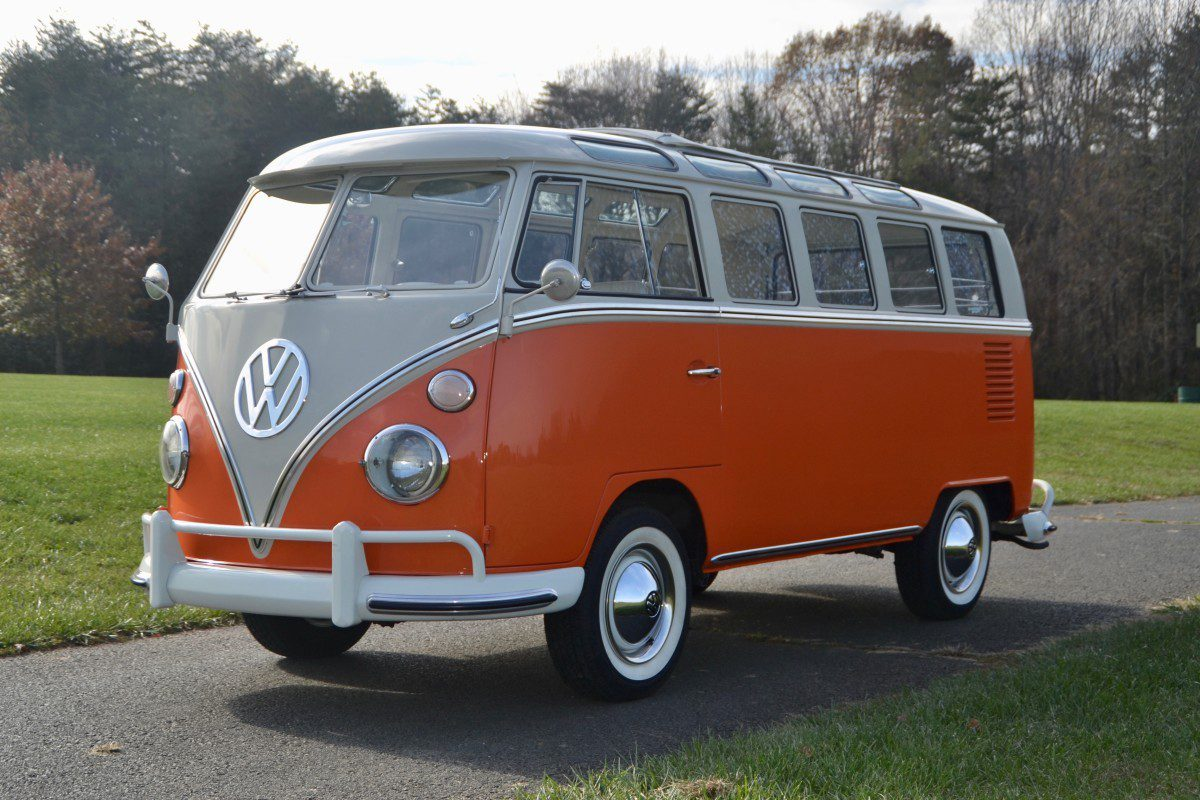 A side view of a first-gen orange VW Bus on an old asphalt road