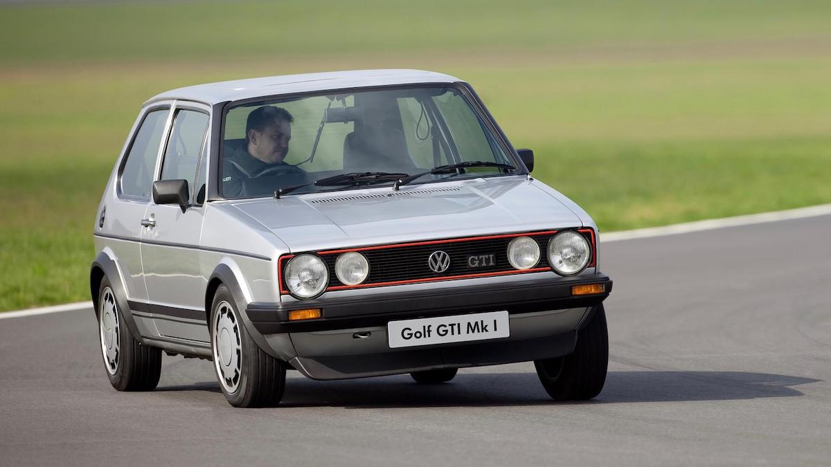A side view fo a Silver MK1 VW Golf GTi on a stretch of road next to a field