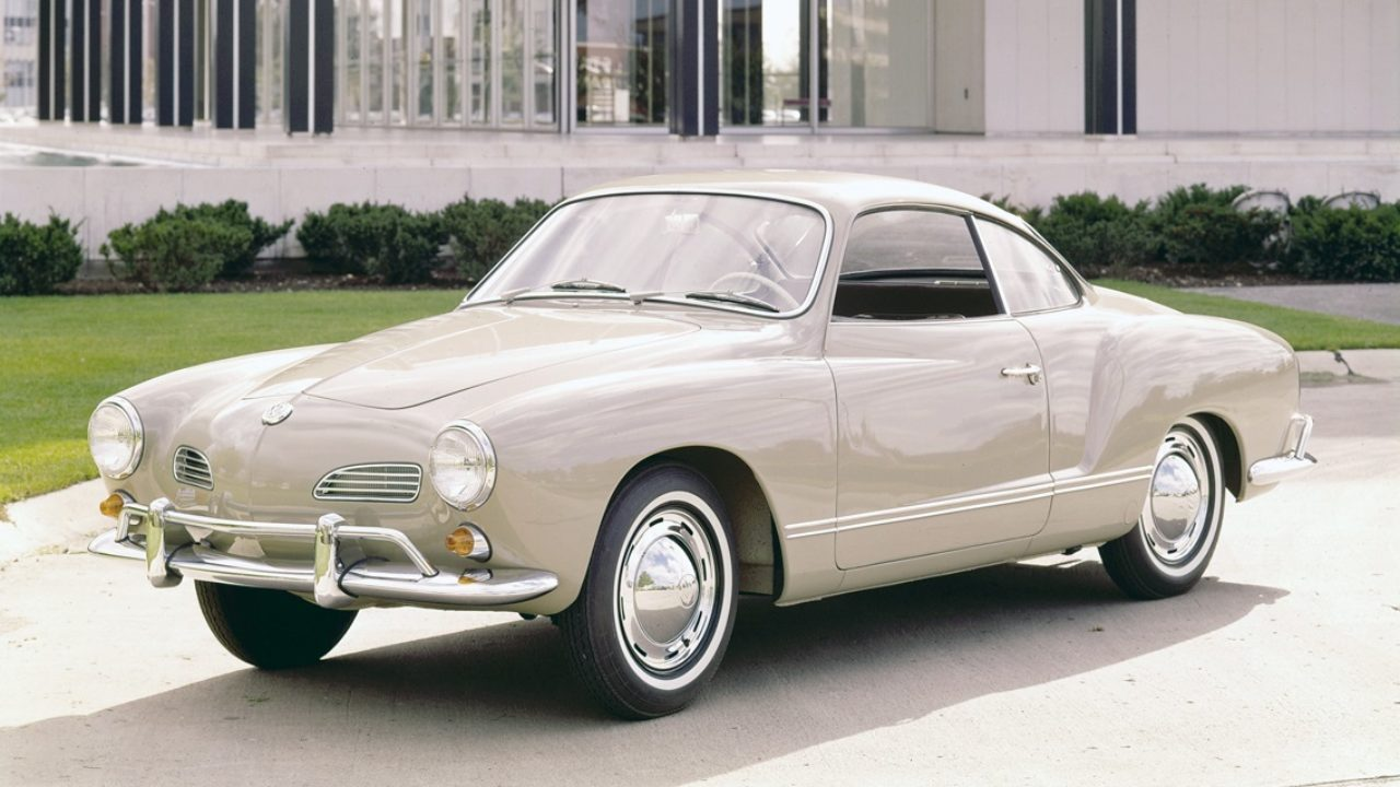 A side view of a 1950s beige VW Karmann-Ghia on white pavement in front of a house