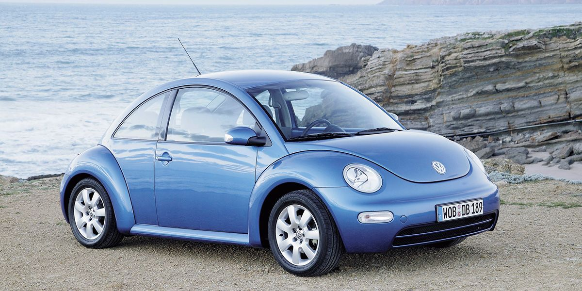A side view of a 1990s blue VW new Beetle parked on the beach next to a body of water
