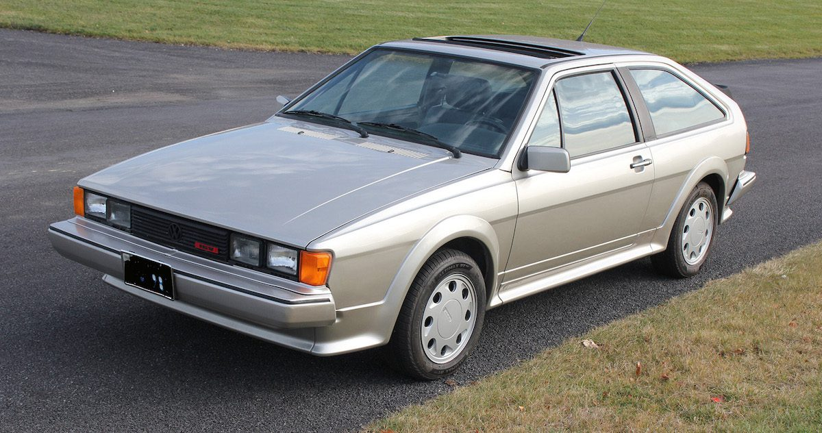A side view of a Second-gen 16V silver VW Scirocco on a black asphalt road